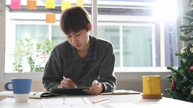 太陽のフレアと窓の近くの彼女のワークスペースでデジタルタブレットに取り組んでいる若い女性のクリエイティブデザイナー。