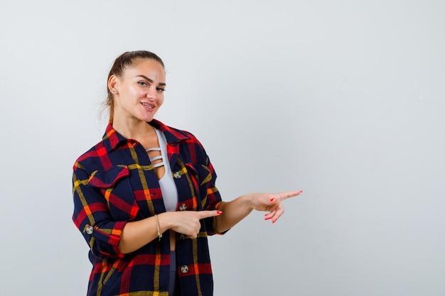 Giovane donna in crop top, camicia a scacchi che punta verso il lato destro e sembra allegra, vista frontale.