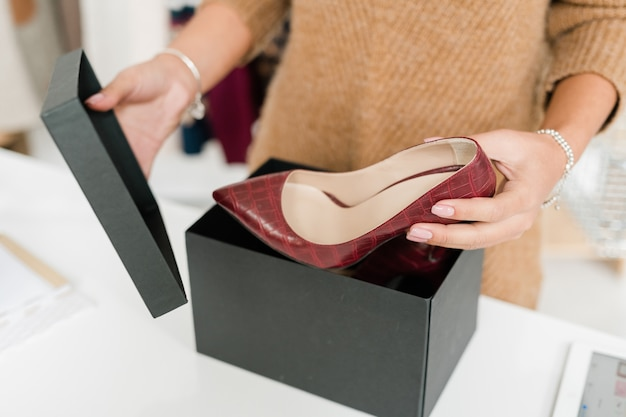 Young female customer unpacking black box and taking out stylish leather shoes on high heels which were ordered in the internet