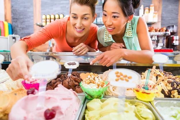 코넷과 콘, 선디를위한 아이스크림을 판매하는 젊은 여성 고객 또는 친구