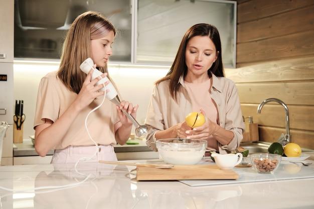 彼女の娘が電気ミキサーで材料を混ぜるつもりである間、若い女性は牛乳でボウルの上にレモンを半分に切る
