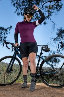 Молодая велосипедистка позирует со своим велосипедом на смотровой площадке с лесистым пейзажем на заднем плане
