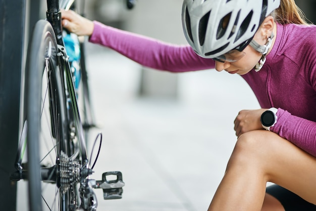 Young female cyclist in protective gear looking focused while checking her bicycle standing outdoors