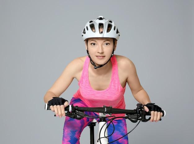灰色の自転車に乗る若い女性サイクリスト