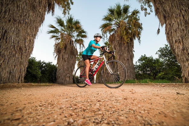 Young female cyclist riding bike on path with palms