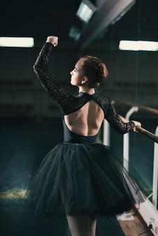 Young female dancer of classic ballet practising in the dance studio