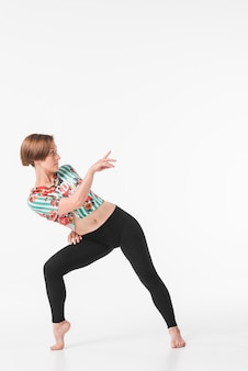 Young female dancer posing against white backdrop