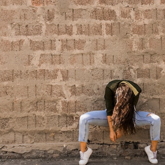 Young female dancer posing in front of wall