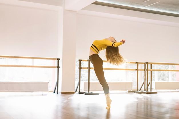 Молодая танцовщица, практикующая в танцевальной студии