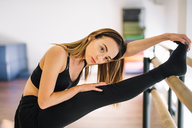 Young female dancer stretching her legs
