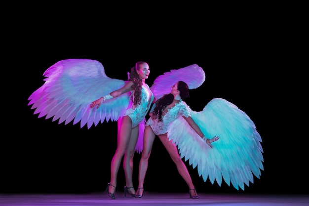 Young female dancer with angel's wings in neon light on black wall