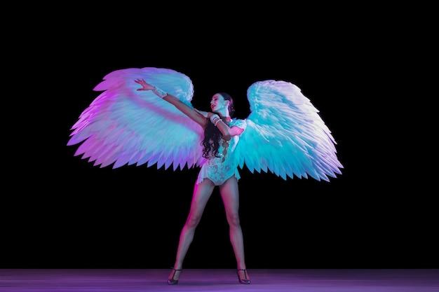 네온 불빛에 천사 날개를 가진 젊은 여성 댄서