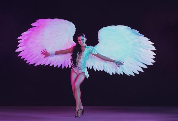 네온 컬러로 하얀 천사의 날개를 가진 젊은 여성 댄서. 우아한 모델, 여성 춤, 포즈. 프리미엄 사진