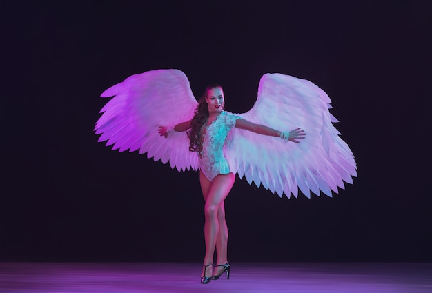 Young female dancer with white angel's wings in neon colors. graceful model, women dancing, posing.