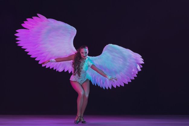 Young female dancer with white angel's wings in purple blue neon light on black wall. graceful model, women dancing, posing. concept of carnival, beauty, motion, overcoming, blooming.