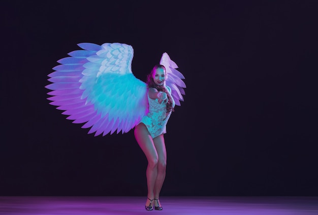 Young female dancer with white angel's wings in purple blue neon light on black wall. graceful model, women dancing, posing.