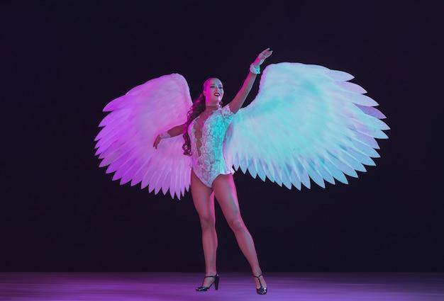 Giovane ballerina con ali di angelo bianco in luce al neon blu viola sul muro nero.
