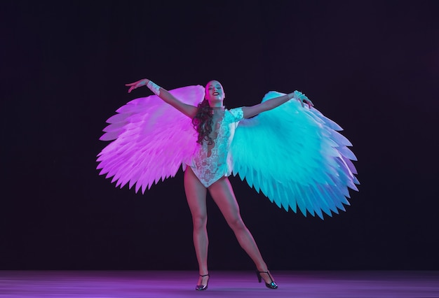 Young female dancer with white angel's wings in purple blue neon light on black wall.