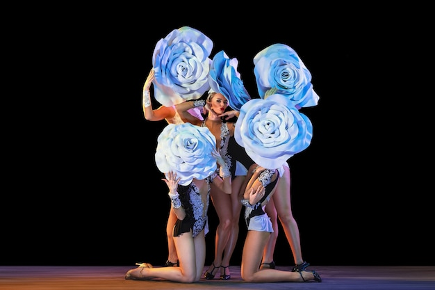Young female dancers with huge floral hats in neon light on black wall