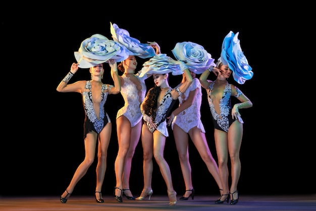 Young female dancers with huge floral hats in neon light on gradient wall