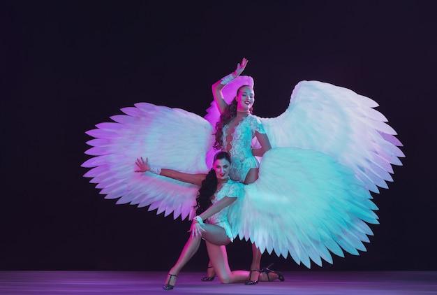 네온 컬러로 하얀 천사의 날개를 가진 젊은 여성 댄서. 우아한 모델, 여성 춤, 포즈.