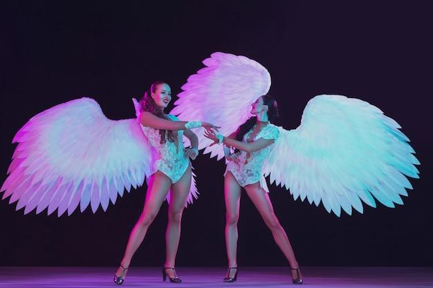 Giovani ballerine con ali d'angelo bianche in luce al neon blu viola sul muro nero.
