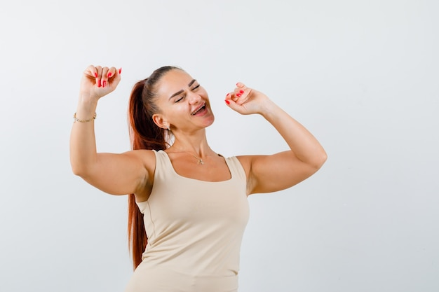 Giovane donna che balla mentre posa in canotta beige e sembra energico, vista frontale.
