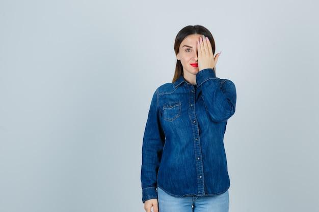 Giovane donna in camicia di jeans e jeans tenendo la mano sugli occhi e guardando carino
