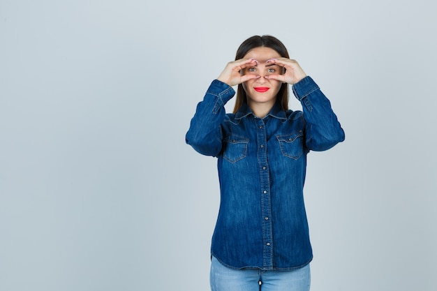 Young female in denim shirt and jeans pretending to peek through binoculars and looking cheery