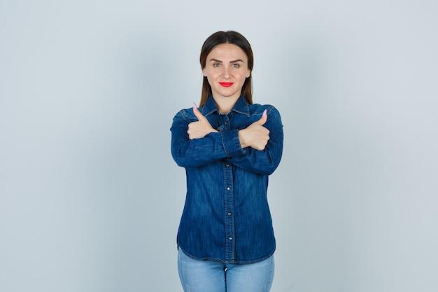 Giovane donna in camicia di jeans e jeans che mostra i pollici incrociati in su e sembra felice