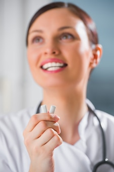Young female dentist doctor holding chewing gum and smiling. oral hygiene concept