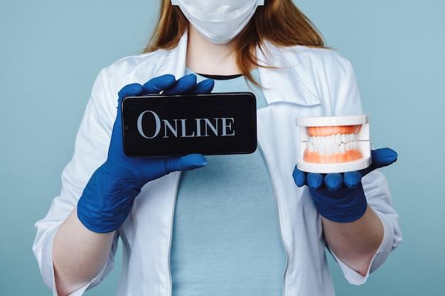 Молодая женщина-дантист в маске и медицинском пальто, держа инструменты и телефон. запись на прием в интернет-клубе.
