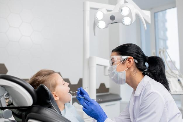 ホワイトコート、保護眼鏡、マスク、手袋を着用した若い女性歯科医が、小さな患者の口腔の口腔検査を行います。