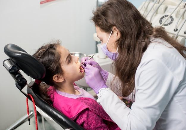若い女性歯科医は歯科医院で患者の女の子の歯をチェックしています。歯科