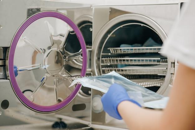젊은 여성 치과 의사는 외과 수술 및 기타 악기 살균을위한 의료 오토 클레이브를 배치합니다.