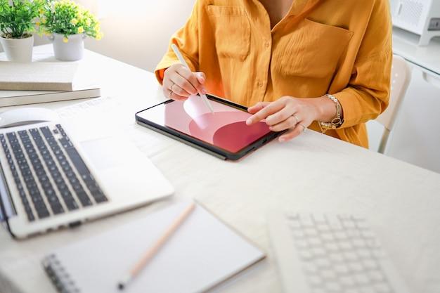Молодая женщина-дизайнер-художник рисует графику для нового дизайна на планшете дома арт-дизайн рисование бизнес и творчество концепция разработки веб-сайтов