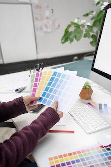 Young female designer choosing the right colors for a logo