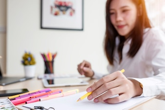 Young female designer creating sketches at office