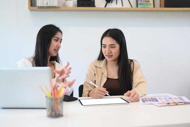 친절한 토론을하고 사무실에서 자신의 프로젝트를 논의하는 젊은 여성 디자이너.