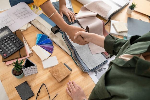 インテリアの若い女性デザイナーと彼女のクライアントがテキスタイルのサンプルで職場を握手