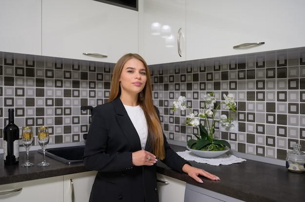 Young female designer or owner at luxury modern black and white kitchen interior with clean design