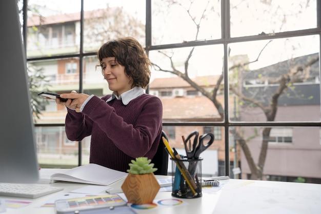 彼女のデザインの写真を撮る若い女性デザイナー