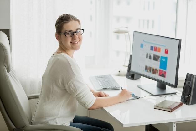 Молодой женский дизайнер, работающий в домашнем офисе на компьютере