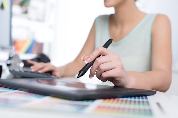 Молодая женщина-дизайнер, работающая с планшетом для рисования