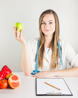 Young female dietician holding green apple with food and clipboard on desk