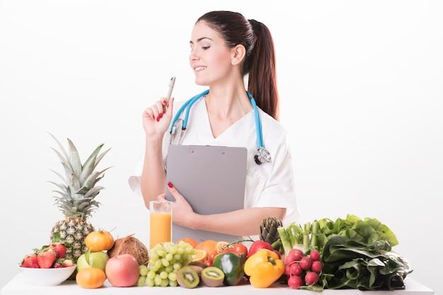 机に座って色とりどりの野菜や果物を見せて若い女性栄養士