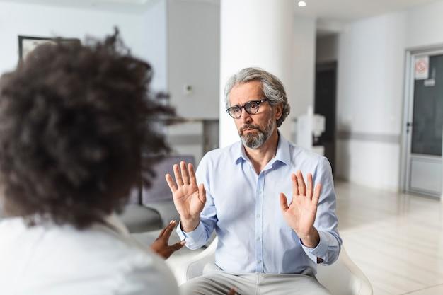 病院の待合室でコミュニケーションをとる若い女性医師と年配の男性。