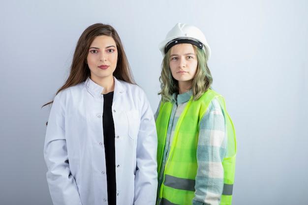 젊은 여성 의사와 여자 엔지니어 흰 벽 위에 서. 고품질 사진
