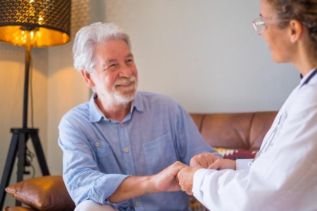 若い女性医師が自宅で年配の男性をチェックして支援しています。医者は年配の患者を助け、ソファに座って世話をします。自宅で引退した老人と女性の在宅介護者