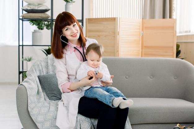 Молодой женский доктор рассматривая маленькую девочку стетоскопом. ребенок в кабинете врача для медицинского обследования